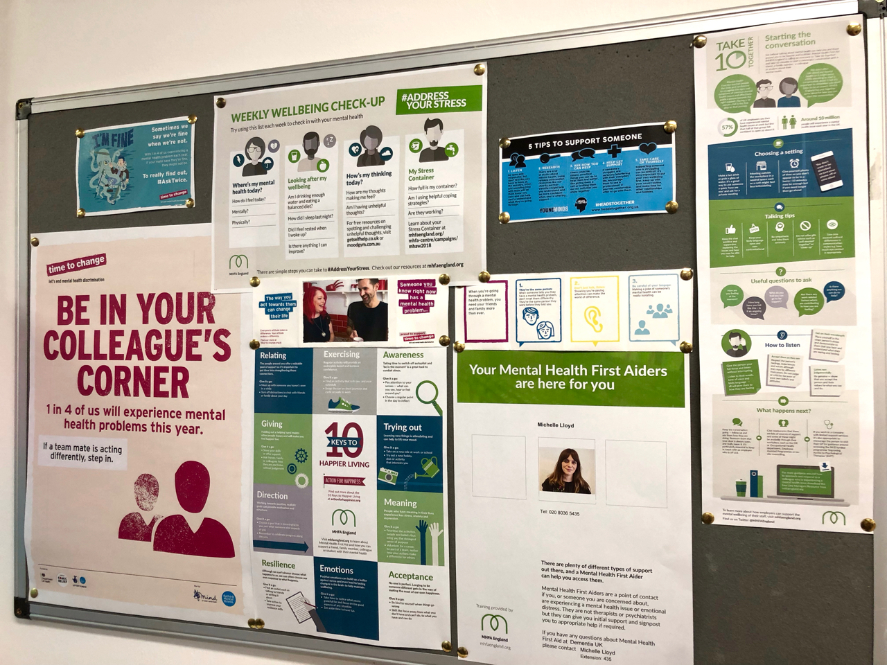 A noticeboard on a kitchen wall, containing posters and leaflets encouraging staff to look out for their colleagues and have conversations about mental health, and informing them who the trained mental health first aider is