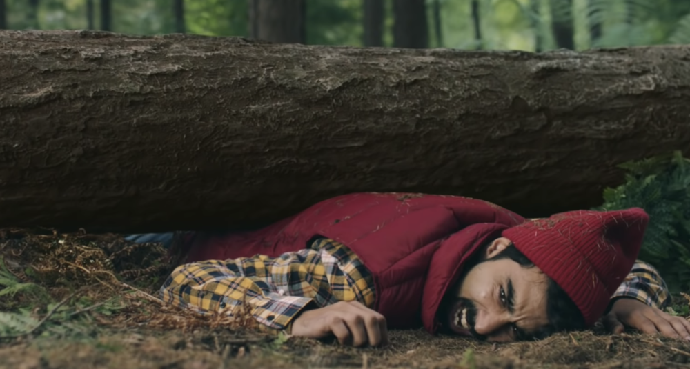 A man trapped under a log in a forest
