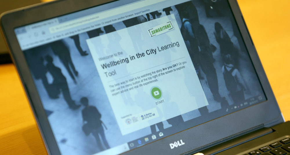 A laptop displaying Samaritans' Wellbeing in the City resource on its screen