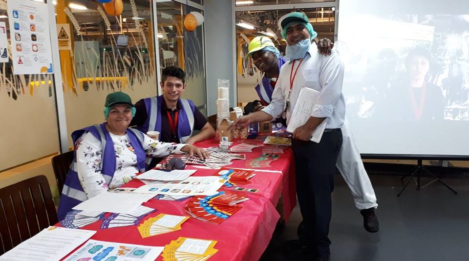 Four employees at Pladis, wearing factory uniforms, smiling around a table of leaflets and posters about mental health