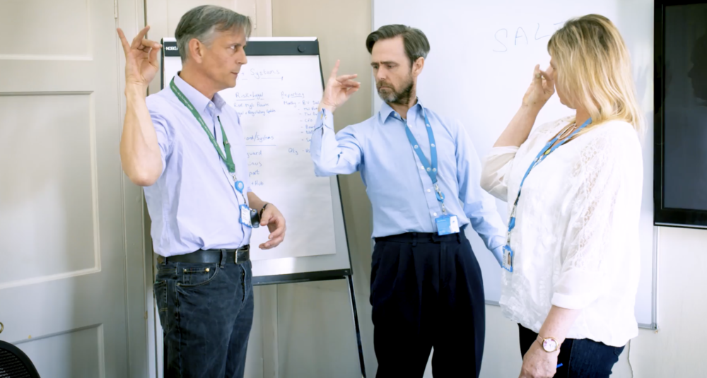 Three colleagues stand near a flipchart making strange gestures and facial expressions