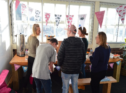 People standing around a table of food and drinks with bunting around it