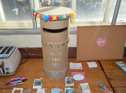 Letter box with 'Split Worry Box' written on it, with cards and pens arranged on table around it