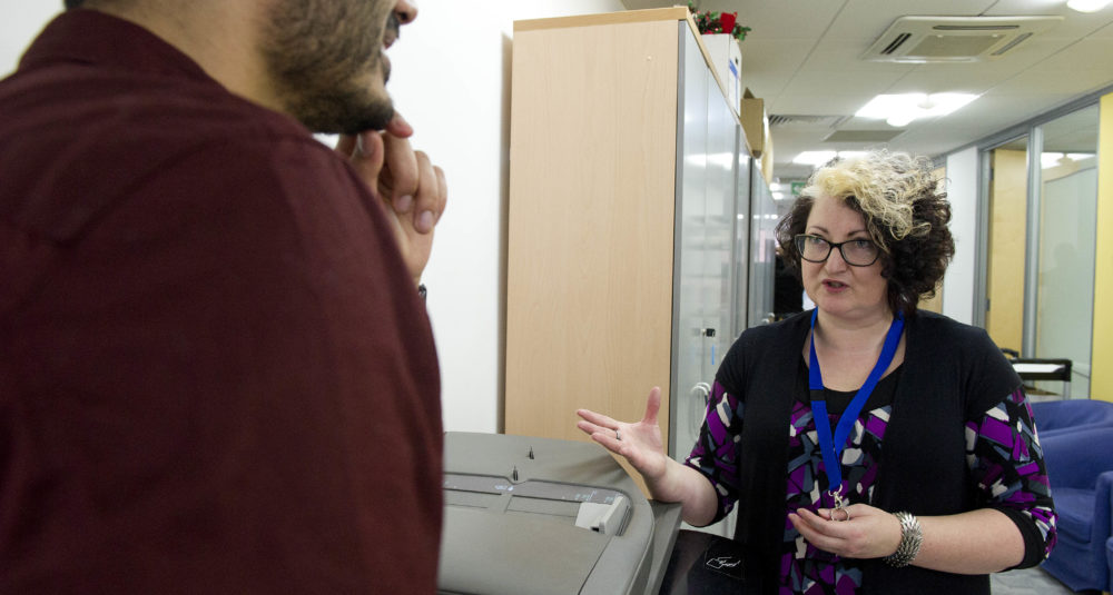 Colleagues talk at a photocopier.