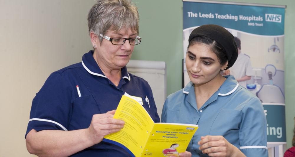 Two nurses discuss treatment of a patient.