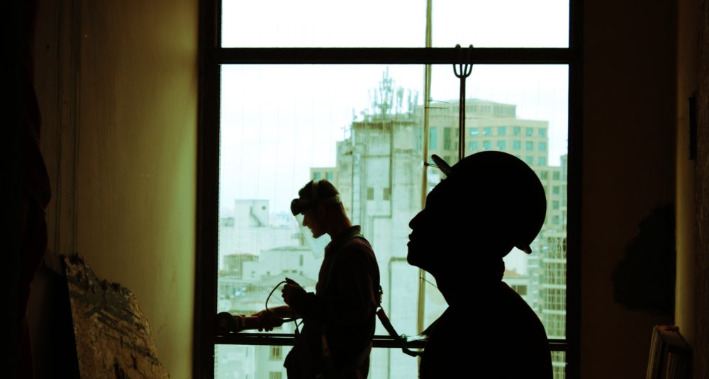 Two men work on a building