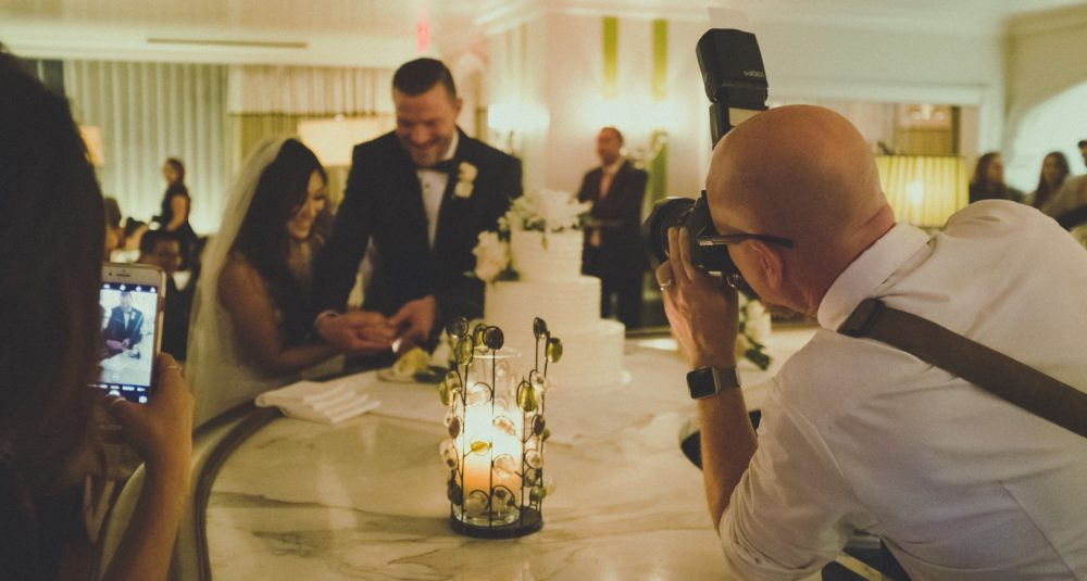 A self-employed wedding photographer snaps the happy couple.