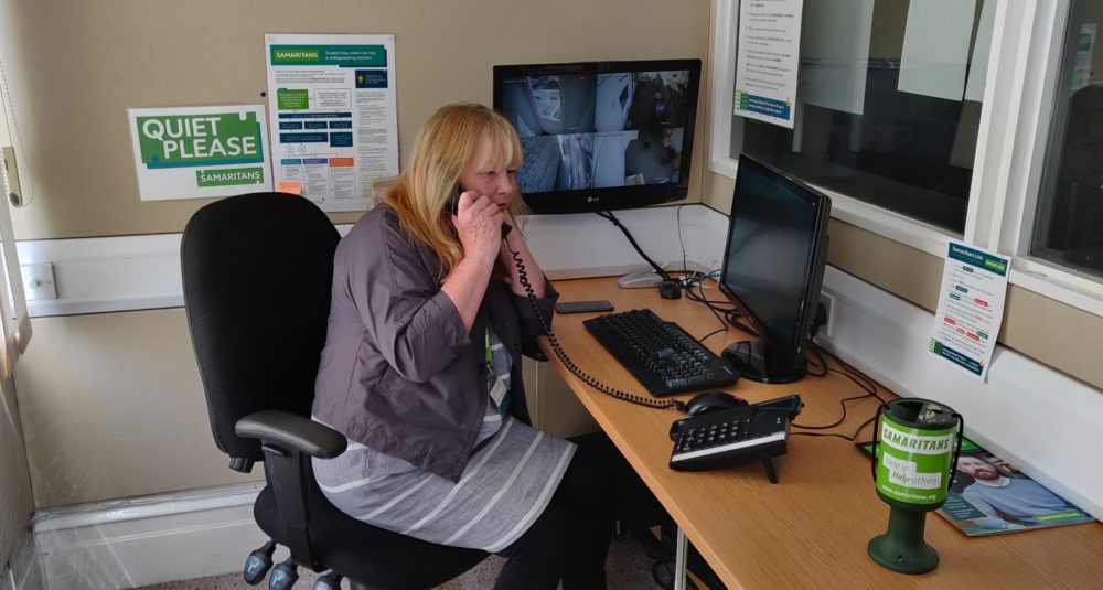 A woman sits at a desk talking on the telephone, with a Samaritans poster behind her