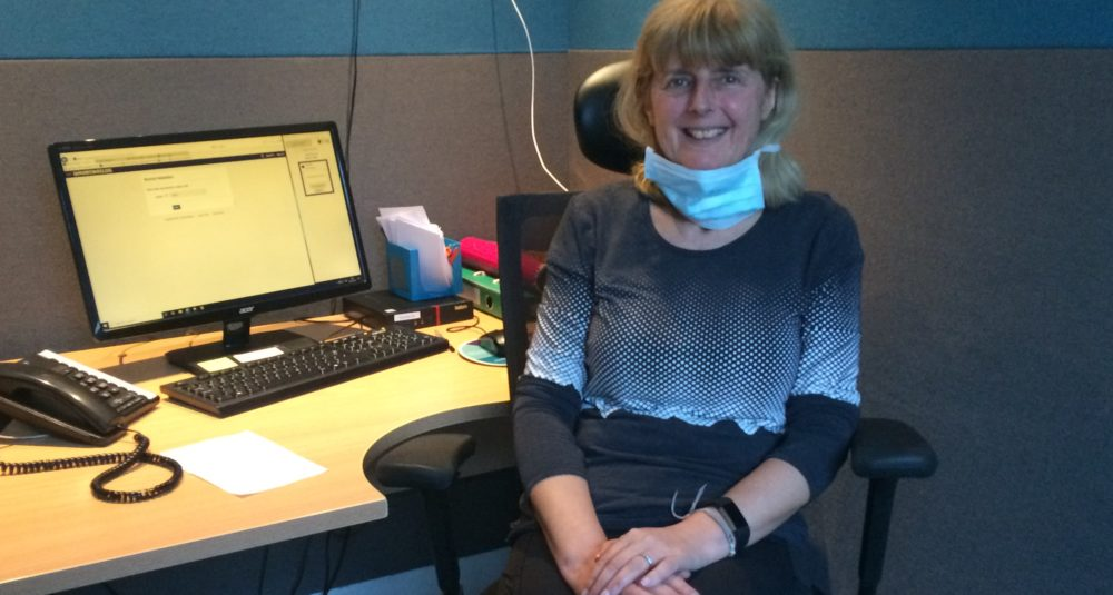 A GP sitting at her desk, wearing a face mask that has been lowered, smiling
