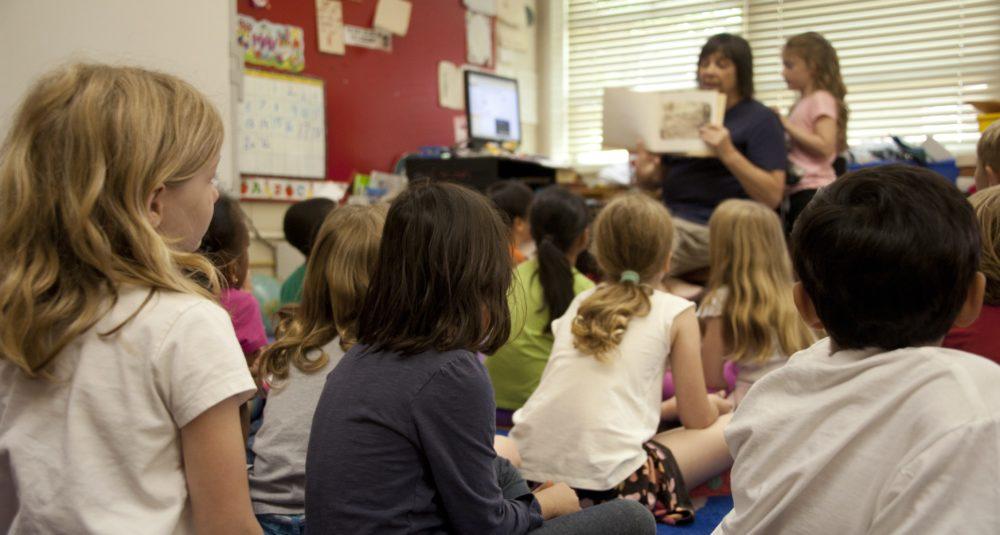A teacher reads a story to her class.