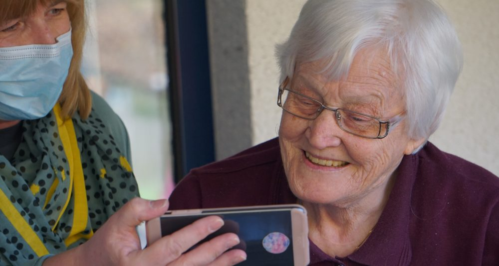 A care worker helps a resident to use a mobile phone.