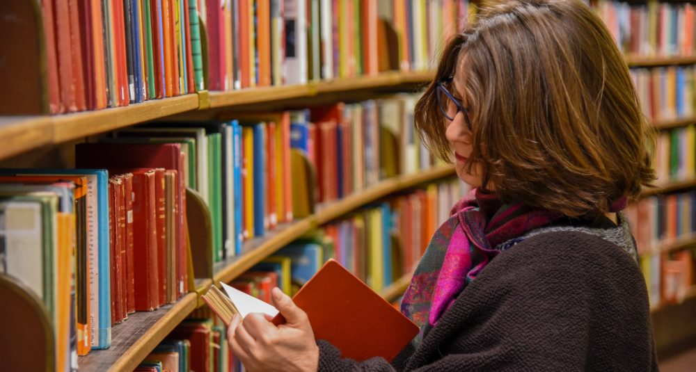 A teacher checks out the books in the school library.