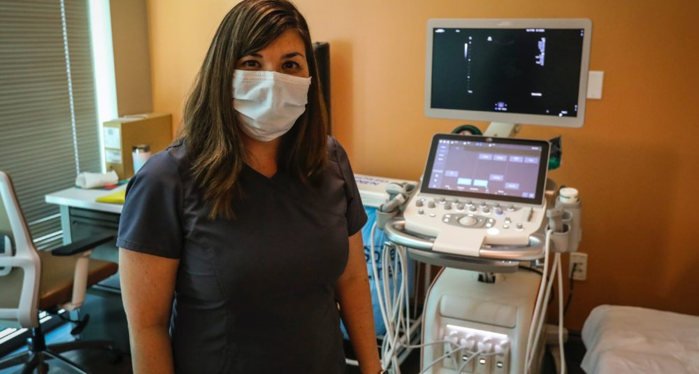 An ultrasound technician stands by her equipment.