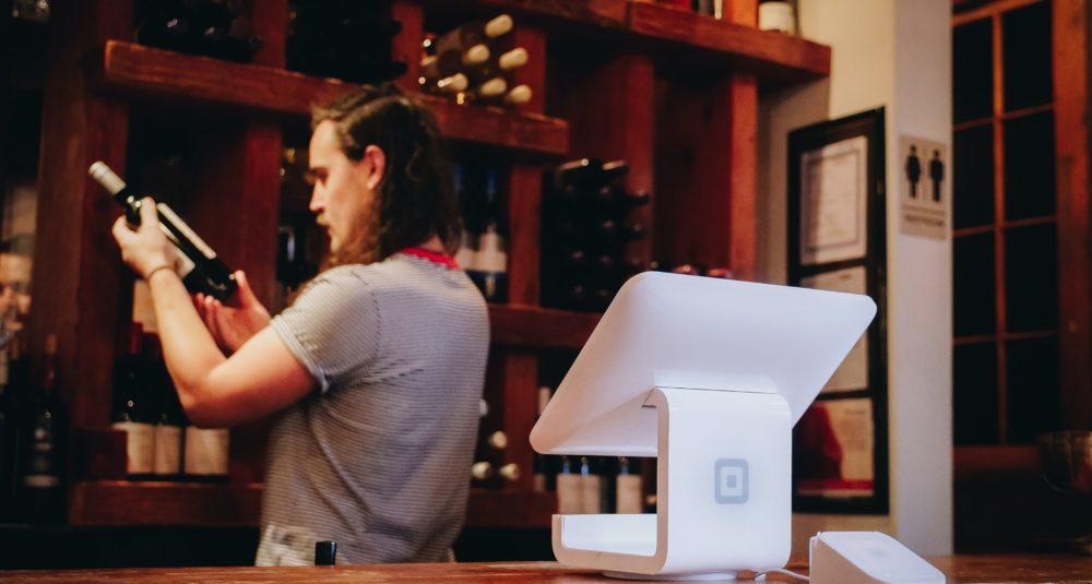 A barman inspects a bottle of wine.