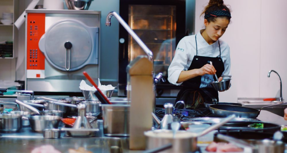 A chef prepares food in a hotel kitchen.