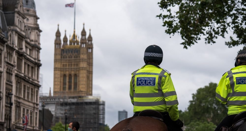 Police watch protesters in London.
