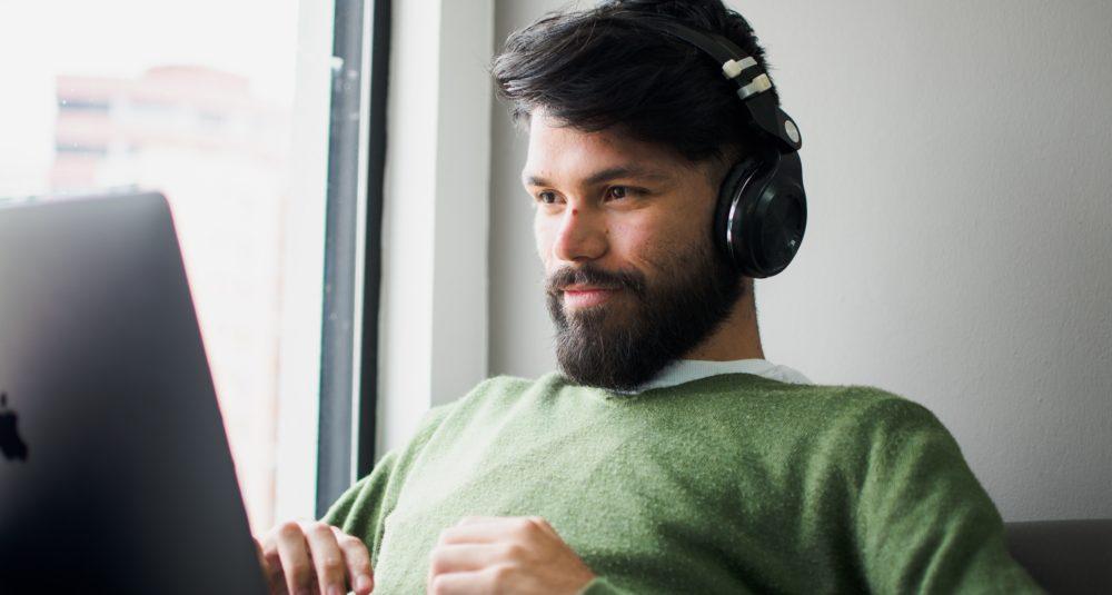 A man smiles at his computer.