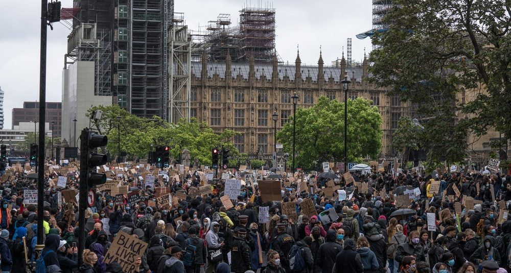 A large crowd of people at a protest outside the Houses of Parliament, with one holding a placard saying Black Lives Matter