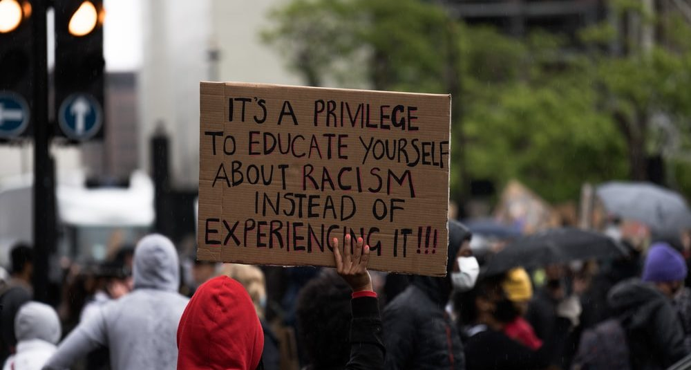 A placard held up at a protest full of people, saying