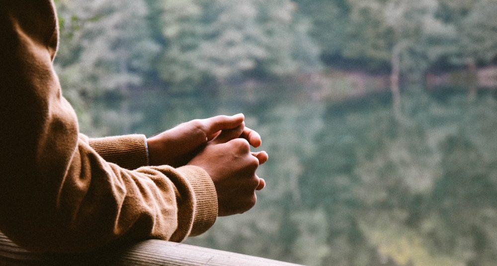 A person's two hands clasped together, leaning on a wooden rail overlooking some water