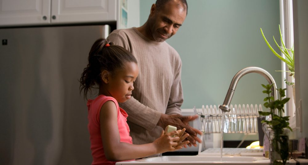 A man teaches his daughter to wash her hands thoroughly