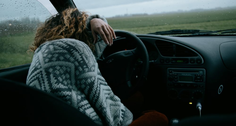 A woman is exhausted in her car.