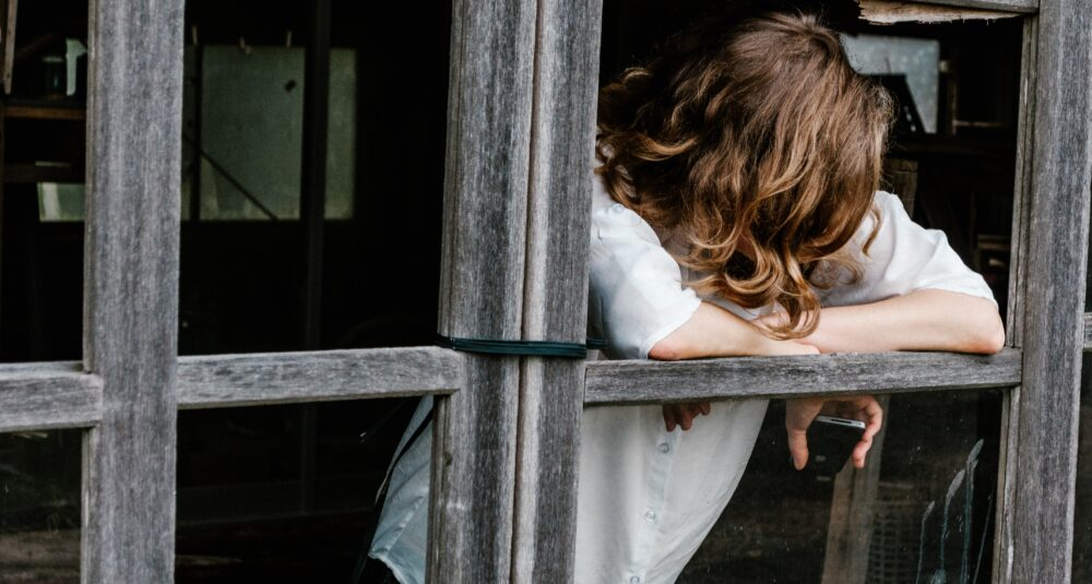 A person leans out of an empty window frame, with their face hidden from view, holding a mobile phone