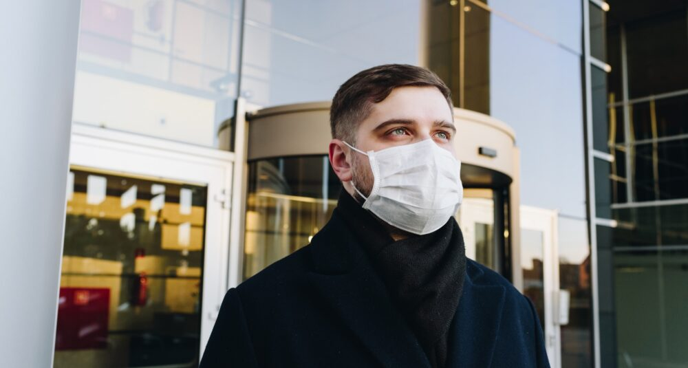 A man returns to his workplace wearing a mask.