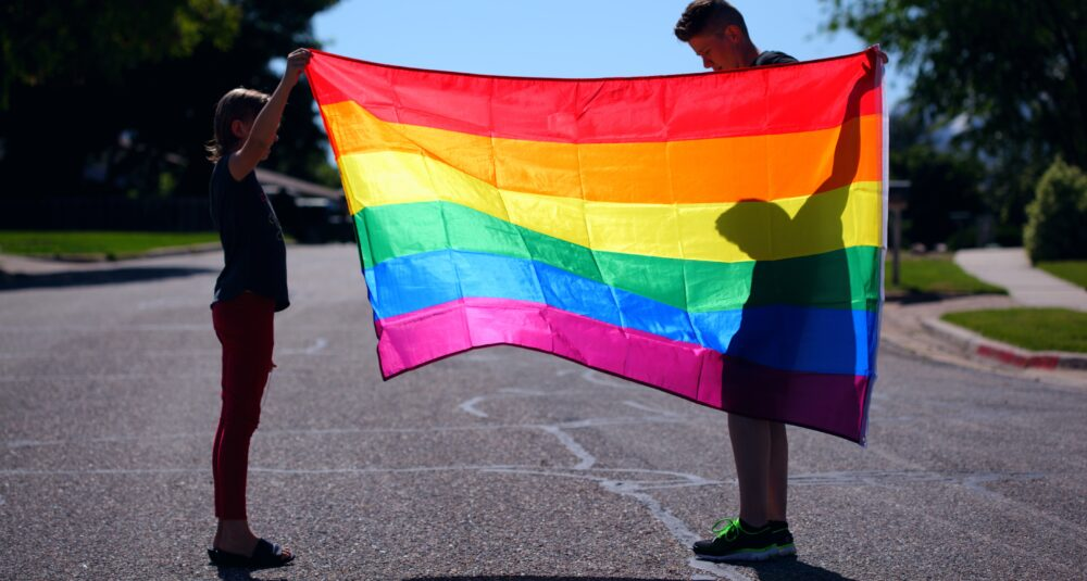 Two people play with an LGBTQ+ Pride flag