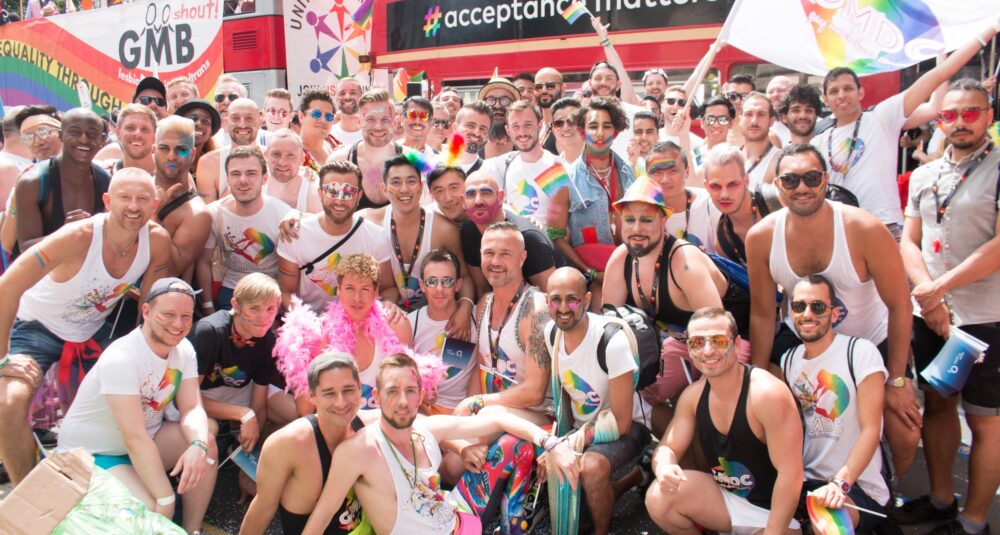 A large group of men wearing rainbow colours and GMCD T-shirts posing in front of a bus saying