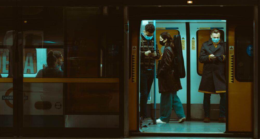 Commuters wear masks on a tube train,