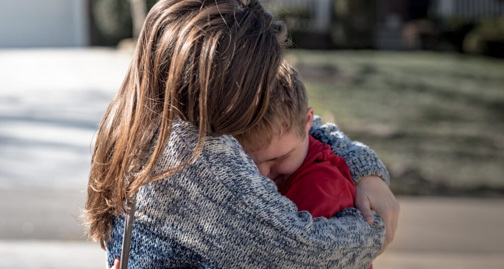 A mother hugs her child.